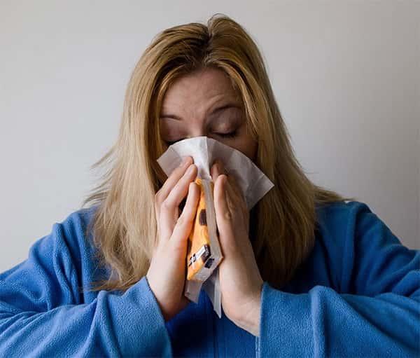 Mulher com Gripe, coriza, assoando o nariz