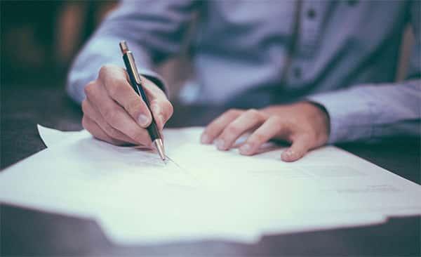 Rapaz com a caneta na mão, escrevendo, estudando