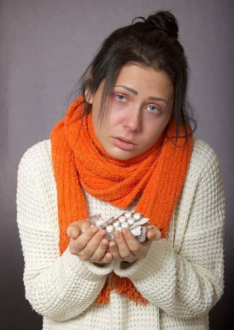 Mulher gripada com medicamentos na mão