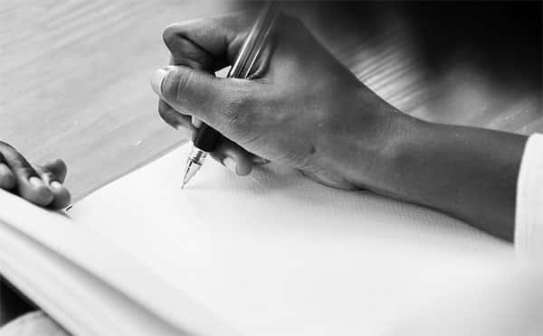 Pessoa iniciando a escrita no caderno