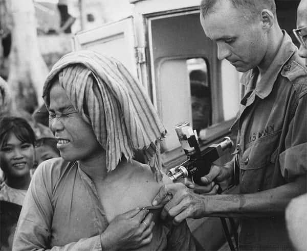 Mulher sendo vacinada por soldado